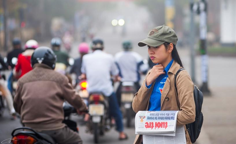 Cô bé sinh viên bán báo trong buổi sáng mờ sương.