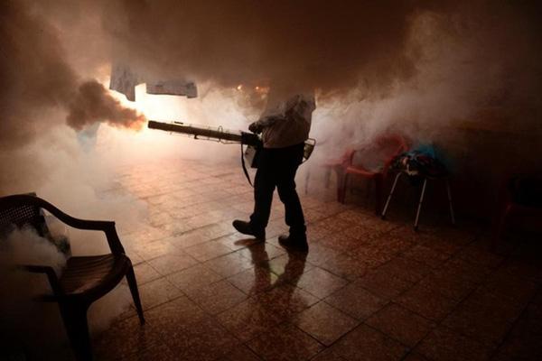 Nhân viên y tế phun thuốc chống muỗi để ngăn sự lây lan của dịch bệnh. Ảnh: AFP